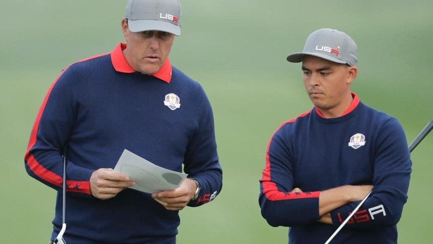 United States' Phil Mickelson talks to United States' Rickie Fowler on the first hole during a foresomes match at the Ryder Cup golf tournament Friday, Sept. 30, 2016, at Hazeltine National Golf Club in Chaska, Minn. (AP Photo/Charlie Riedel)
