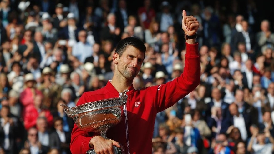FILE - In this Sunday, June 5, 2016 file photo, Serbia's Novak Djokovic holds the trophy after winning the final of the French Open tennis tournament against Britain's Andy Murray, at the Roland Garros stadium in Paris, France. Novak Djokovic on Friday, Sept. 30 says Grand Slam trophies and the No. 1 ranking are no longer his priority. The top-ranked Serb, who has won 12 major titles, says he felt emotionally drained after winning the French Open in June for his first Grand Slam title at Roland Garros and his fourth in a row. (AP Photo/Michel Euler, file)