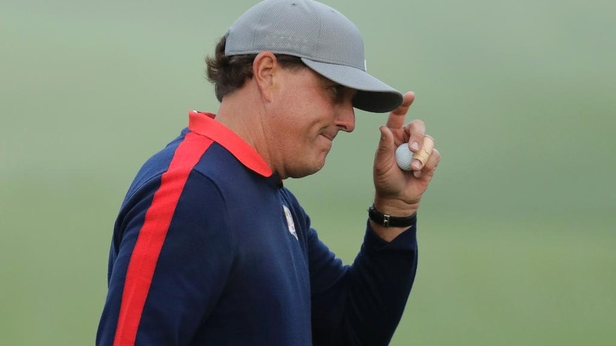 United States' Phil Mickelson tips his hat after making a putt on the first hole during a foresomes match at the Ryder Cup golf tournament Friday, Sept. 30, 2016, at Hazeltine National Golf Club in Chaska, Minn. (AP Photo/Charlie Riedel)
