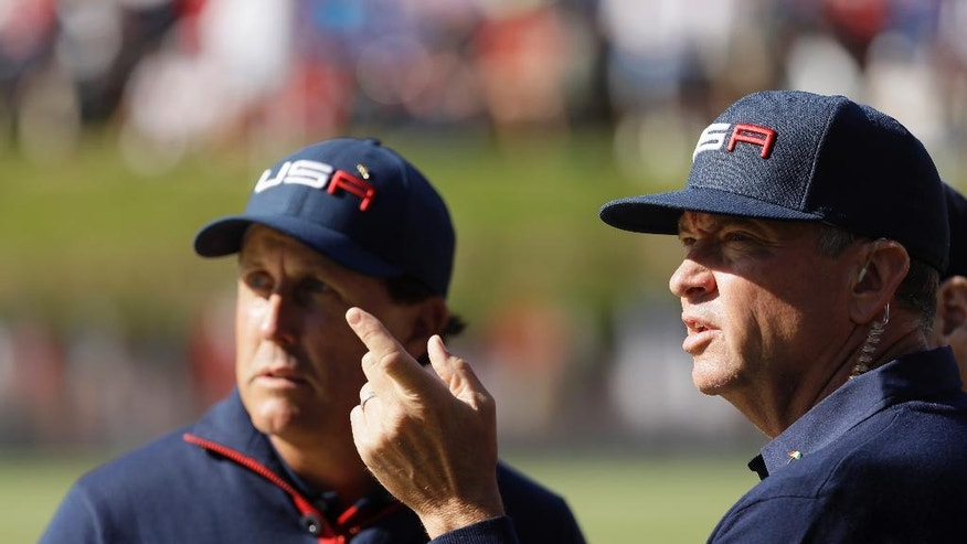 United States captain Davis Love III talks to United States' Phil Mickelson on the 16th hole during a foresomes match at the Ryder Cup golf tournament Saturday, Oct. 1, 2016, at Hazeltine National Golf Club in Chaska, Minn. (AP Photo/David J. Phillip)