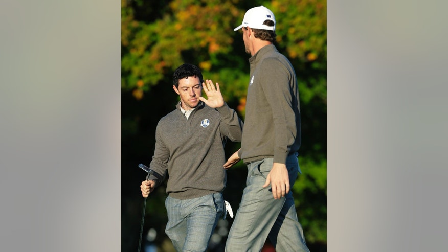 Europe's Rory McIlroy high fives Europe's Thomas Pieters on the second hole during a foresomes match at the Ryder Cup golf tournament Saturday, Oct. 1, 2016, at Hazeltine National Golf Club in Chaska, Minn. (AP Photo/Charlie Riedel)