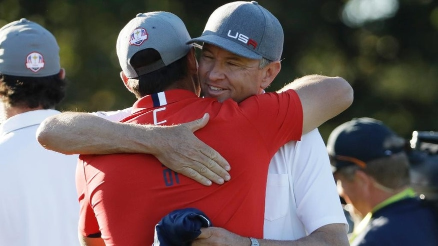 United States captain Davis Love III hugs United States' Brooks Koepka after he won his match during a four-balls match at the Ryder Cup golf tournament Friday, Sept. 30, 2016, at Hazeltine National Golf Club in Chaska, Minn. (AP Photo/David J. Phillip)