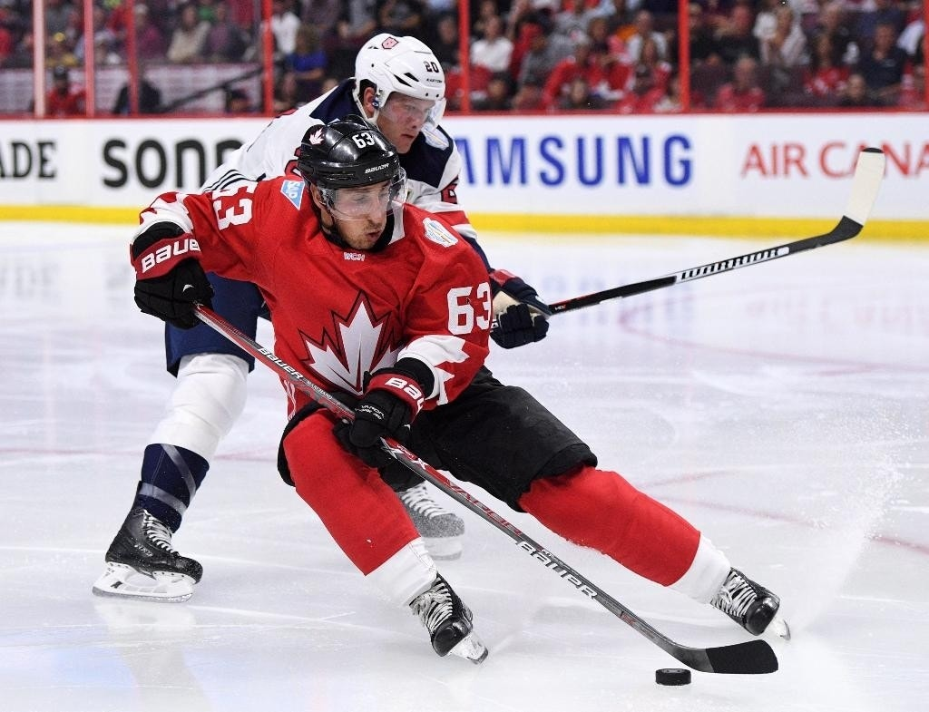 FILE - In this Sept. 10, 2016, file photo, Canada's Brad Marchand skates with the puck as United States' Ryan Suter tries to push him off it during the second period of an exhibition World Cup of Hockey game in Ottawa, Ontario, on The World Cup of Hockey is going to help some of the league's top stars start the season at a high level, coming off a best-on-best tournament. (Sean Kilpatrick/The Canadian Press via AP, File)