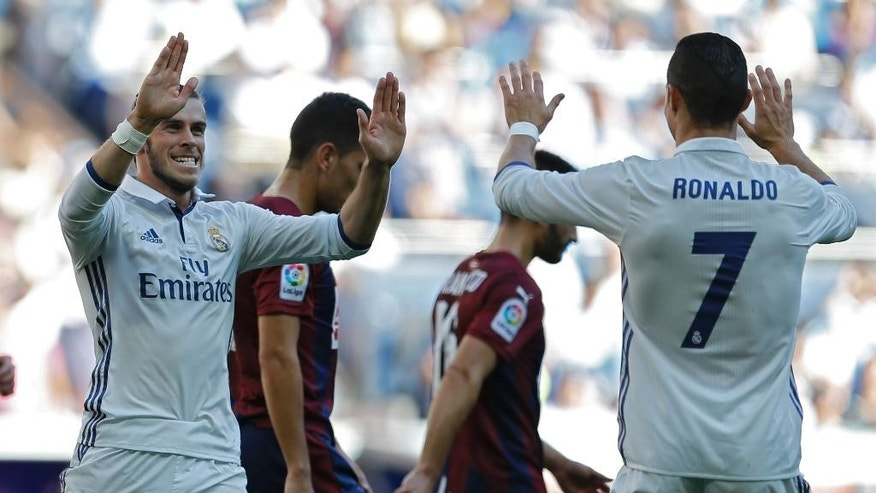 Real Madrid's Gareth Bale, left, celebrates with teammate Cristiano Ronaldo after scoring their side's first goal against Eibar during the Spanish La Liga soccer match between Real Madrid and Eibar at the Santiago Bernabeu stadium in Madrid, Sunday, Oct. 2, 2016. (AP Photo/Francisco Seco)