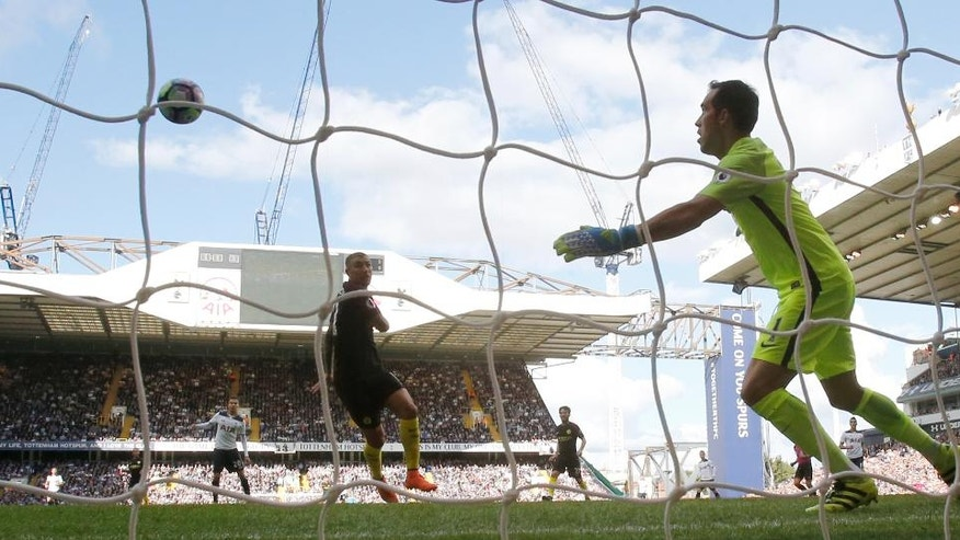 Manchester City's Aleksandar Kolarov, left, watches as the ball defects off him past Manchester City's goalkeeper Claudio Bravo, as he scores an own goal for the opening goal of the game during the Premier League soccer match between Tottenham Hotspur and Manchester City at White Hart Lane stadium in London, Sunday, Oct. 2, 2016. (AP Photo/Frank Augstein)