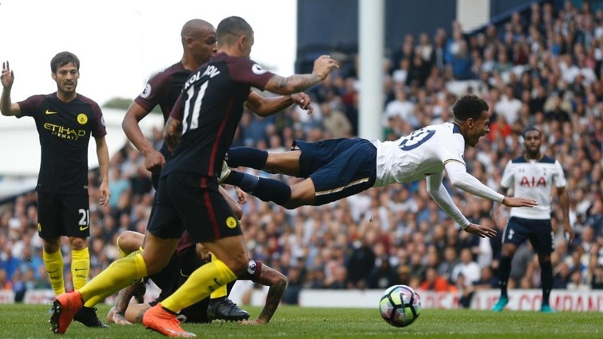 Tottenham Hotspur's Dele Alli, right, goes airborne after being found by Manchester City's Nicolás Otamendi, who was show a yellow card for the tackle. during the Premier League soccer match between Tottenham Hotspur and Manchester City at White Hart Lane stadium in London, Sunday, Oct. 2, 2016. (AP Photo/Frank Augstein)
