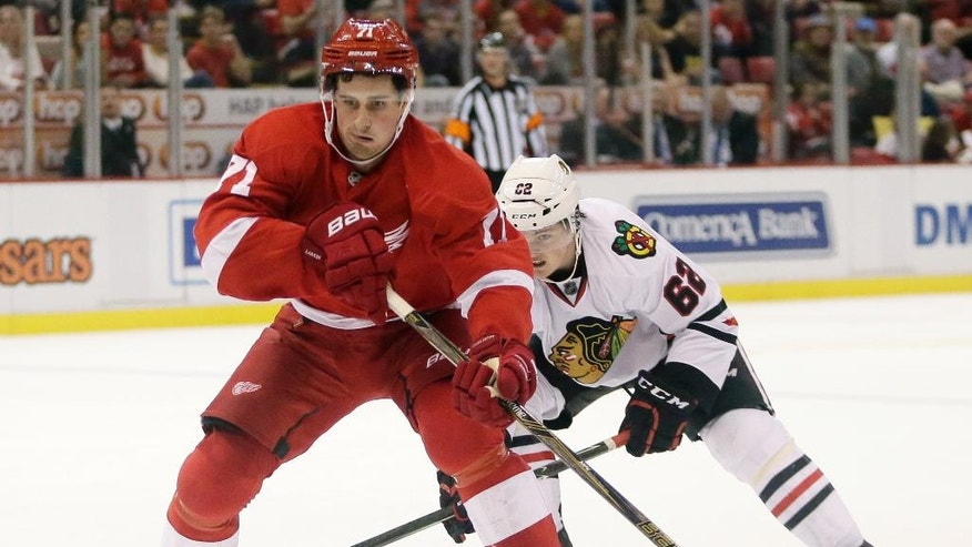 Detroit Red Wings center Dylan Larkin (71) is pursued by Chicago Blackhawks center Luke Johnson (62) during the second period of an NHL hockey game, Sunday, Oct. 2, 2016, in Detroit. (AP Photo/Duane Burleson)