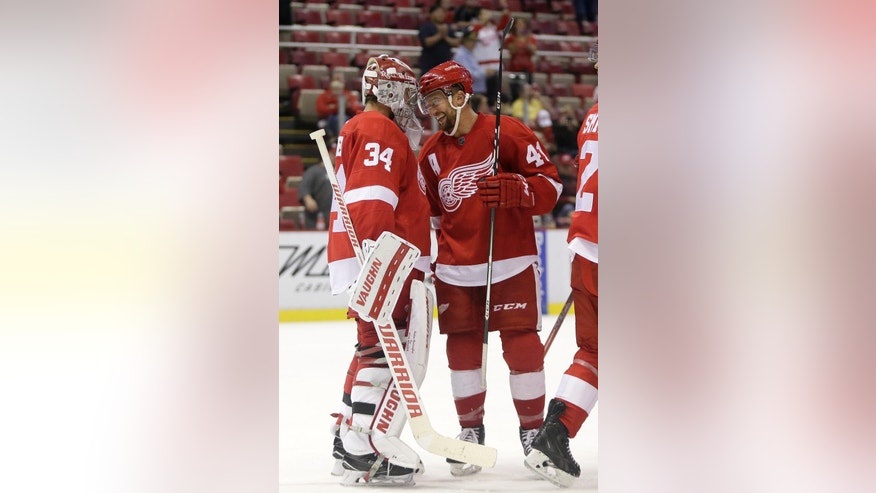 Detroit Red Wings goalie Petr Mrazek (34), of the Czech Republic, celebrates with center Luke Glendening (41) after a 6-3 win over the Chicago Blackhawks in an NHL hockey game Sunday, Oct. 2, 2016, in Detroit. The Red Wings defeated the Blackhawks 6-3. (AP Photo/Duane Burleson)