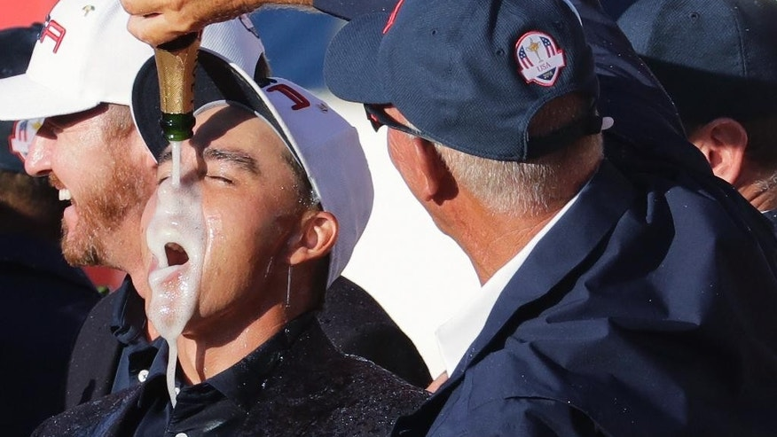 United States' Rickie Fowler drinks champagne during the closing ceremony of the Ryder Cup golf tournament Sunday, Oct. 2, 2016, at Hazeltine National Golf Club in Chaska, Minn. (AP Photo/Charlie Riedel)