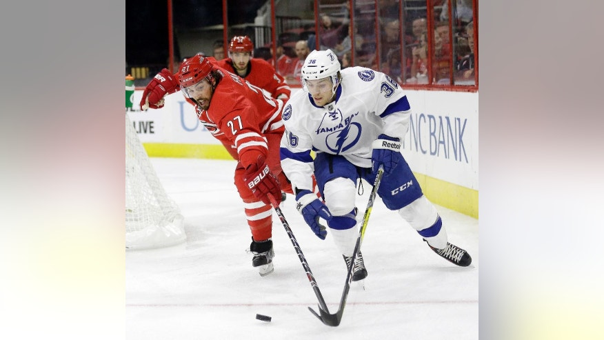 Carolina Hurricanes' Justin Faulk (27) and Tampa Bay Lightning's Brayden Point (36) chase the puck during the first period of an exhibition NHL hockey game in Raleigh, N.C., Friday, Sept. 30, 2016. (AP Photo/Gerry Broome)