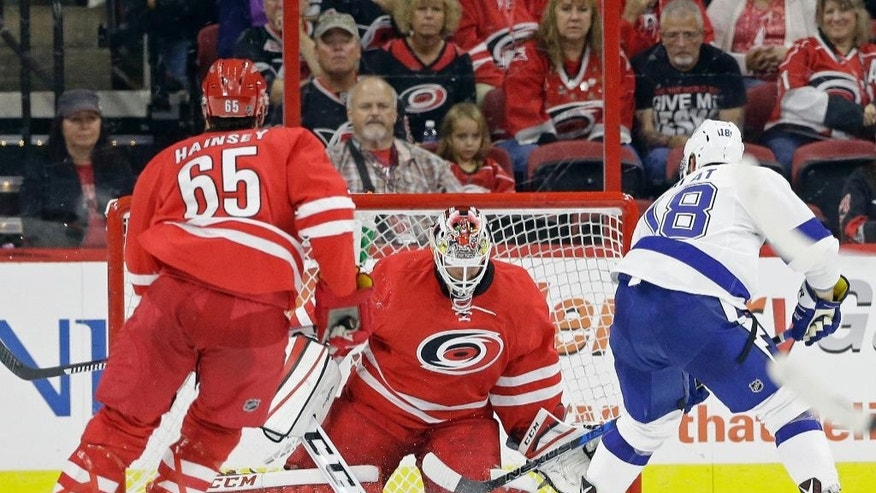 Tampa Bay Lightning's Ondrej Palat (18), of the Czech Republic, scores during overtime against Carolina Hurricanes goalie Michael Leighton as Hurricanes' Ron Hainsey (65) watches in an exhibition NHL hockey game in Raleigh, N.C., Friday, Sept. 30, 2016. Tampa Bay won 2-1. (AP Photo/Gerry Broome)