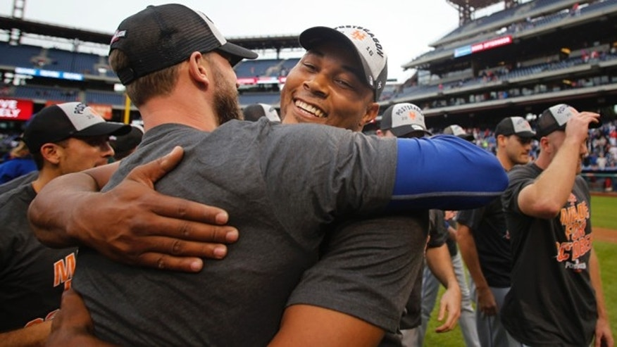 New York Mets relief pitcher Jeurys Familia, right, is embraced by a teammate after the Mets defeated the Philadelphia Phillies 5-3 in a baseball game securing a wildcard playoff slot, Saturday, Oct. 1, 2016, in Philadelphia. (AP Photo/Laurence Kesterson)