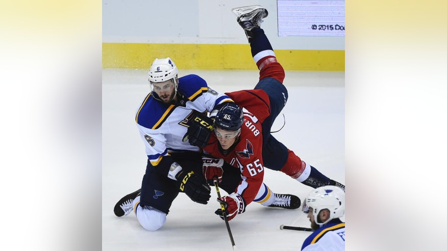 Washington Capitals left wing Andre Burakovsky (65), of Austria, trips over St. Louis Blues defenseman Joel Edmundson (6) while chasing the puck during third period of an NHL preseason hockey game, Monday, Oct. 3, 2016, in Washington. The Capitals won 2-1 in a shoot out. (AP Photo/Molly Riley)