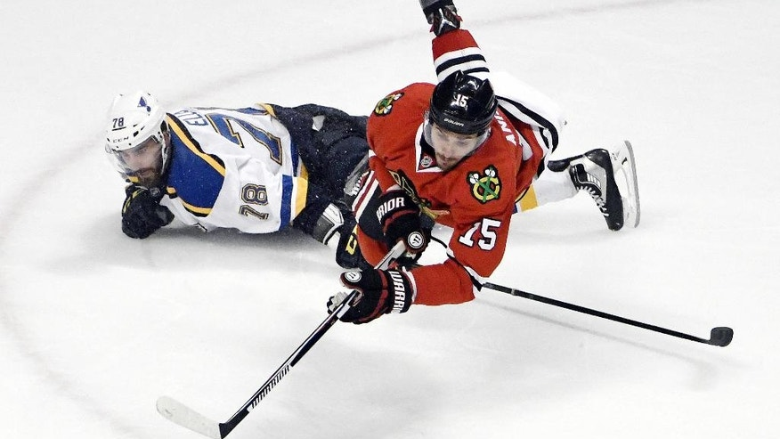 Chicago Blackhawks center Artem Anisimov (15) dives for the puck over St. Louis Blues defenseman Morgan Ellis (78) during the third period of an NHL hockey preseason game Saturday, Oct. 1, 2016, in Chicago.  The Blackhawks won 4-0. (AP Photo/David Banks)