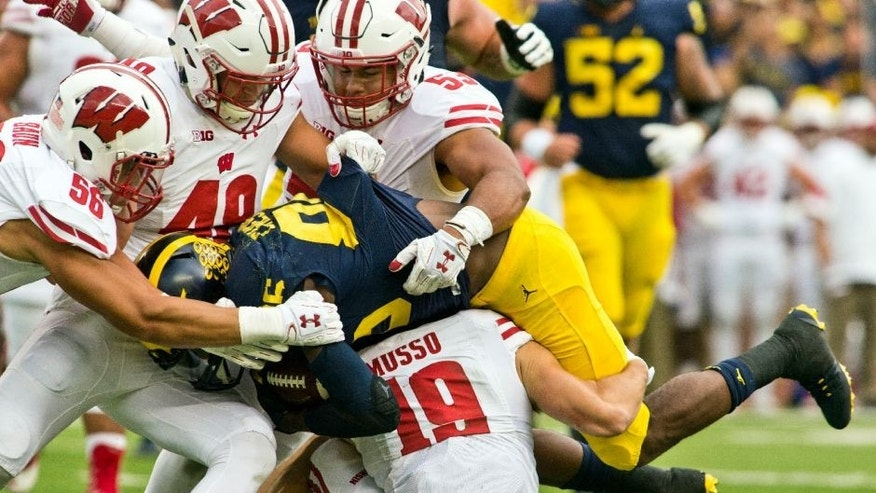 Michigan wide receiver Jehu Chesson, center, is gang-tackled by Wisconsin defenders Zack Baun, Jack Cichy, T.J. Edwards and Leo Musso in the first quarter.