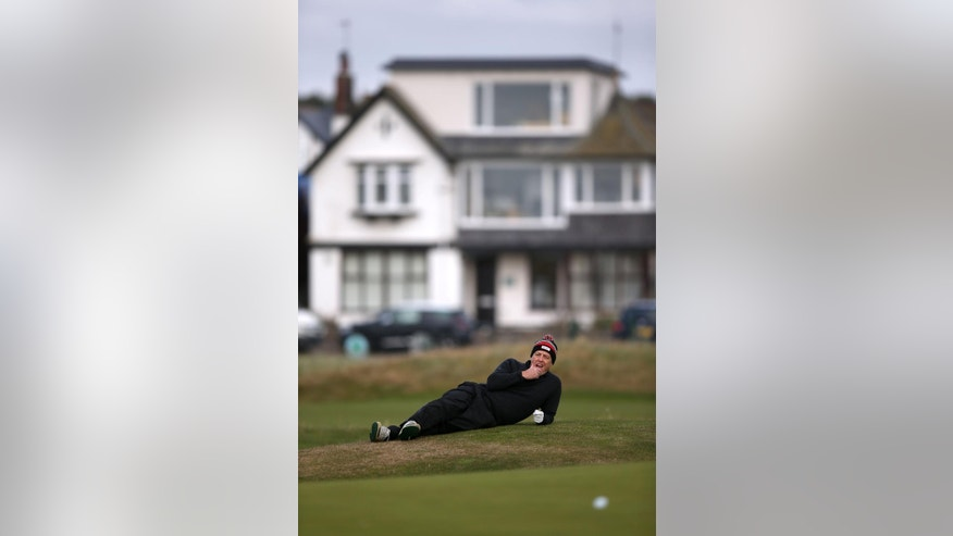 Actor Hugh Grant lays down by the side of the 16th green, during day one of the Dunhill Links Championship, at Carnoustie Golf Links, in Scotland, Thursday Oct. 6, 2016. (Jane Barlow/PA via AP)