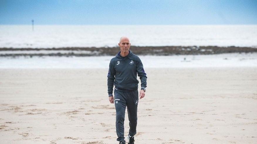 Bob Bradley the new team manager of English Premier League soccer team Swansea City walks on the beach after a press conference at the Marriott Hotel, in Swansea, Wales Friday Oct. 7, 2016. Bradley is the first American to manage an English Premier League team. (Simon Galloway/PA via AP)
