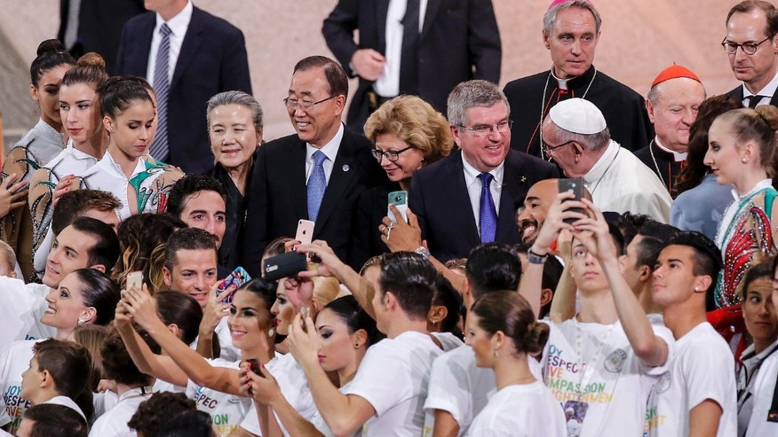 Pope Francis, U.N. Secretary General Ban Ki-moon and IOC President Thomas Bach stand in between participants in the international conference on sports and faith