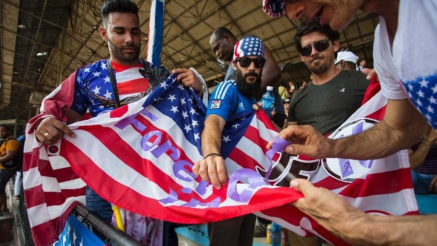 Fans arrange a message on a U.S. national flag in preparation for a friendly soccer match between Cuba and the United States, at the Pedro Marrero Stadium in Havana, Cuba, Friday, Oct. 7, 2016. The U.S. beat Cuba 0-2.  (AP Photo/Desmond Boylan)