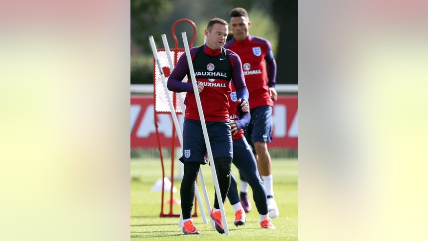 England's Wayne Rooney, center, attends a training session at Enfield Training Ground, London, Monday Oct. 10, 2016. England will play Slovenia in a World Cup qualifier on Tuesday. (Andrew Matthews/PA via AP)