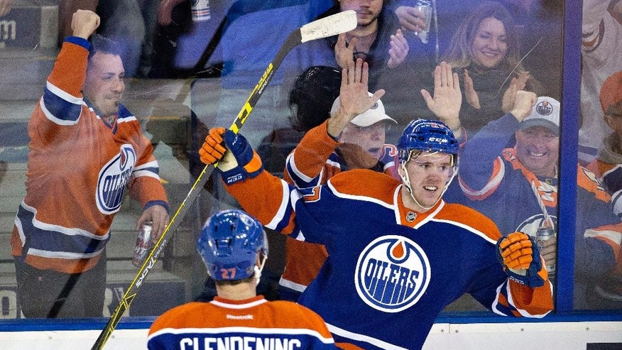 FILE - In this Feb. 2, 2016, file photo, Edmonton Oilers' Connor McDavid (97) and Adam Clendening (27) celebrate McDavid's goal against the Columbus Blue Jackets during the second period of an NHL hockey game in Edmonton, Alberta. McDavid is elite at 19 years old, and going into his second pro season with the Edmonton Oilers is already knocking on the door of being the best hockey player in the world.  (Jason Franson/The Canadian Press via AP, File)