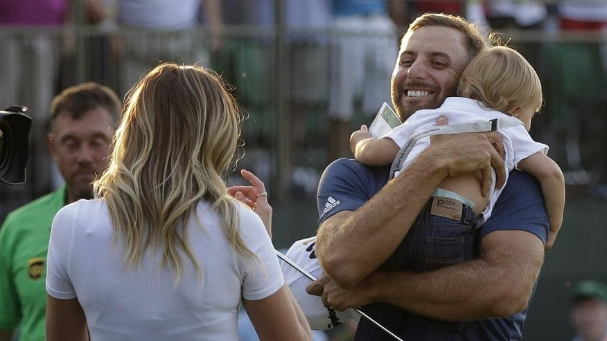 FILE - In this June 19, 2016, file photo, Dustin Johnson, right, greets his fiance, Paulina Gretzky, as he holds their son, Tatum Gretzky, on the 18th hole during the final round of the U.S. Open golf championship,  at Oakmont Country Club, in Oakmont, Pa. Johnson made it a clean sweep of the tour's biggest honors that are named after its most prominent players. He won the Jack Nicklaus Award as player of the year, the Arnold Palmer Award for leading the money list and the Byron Nelson Award for having the lowest adjusted scoring average. (AP Photo/John Minchillo, File)