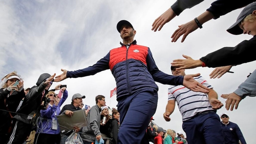 FILe - In this Sept. 27, 2016, file photo, United States' Dustin Johnson is greeted by fans as he walks to the eighth hole during a practice round for the Ryder Cup golf tournament, at Hazeltine National Golf Club in Chaska, Minn. Johnson made it a clean sweep of the tour's biggest honors that are named after its most prominent players. He won the Jack Nicklaus Award as player of the year, the Arnold Palmer Award for leading the money list and the Byron Nelson Award for having the lowest adjusted scoring average. (AP Photo/Charlie Riedel, File)