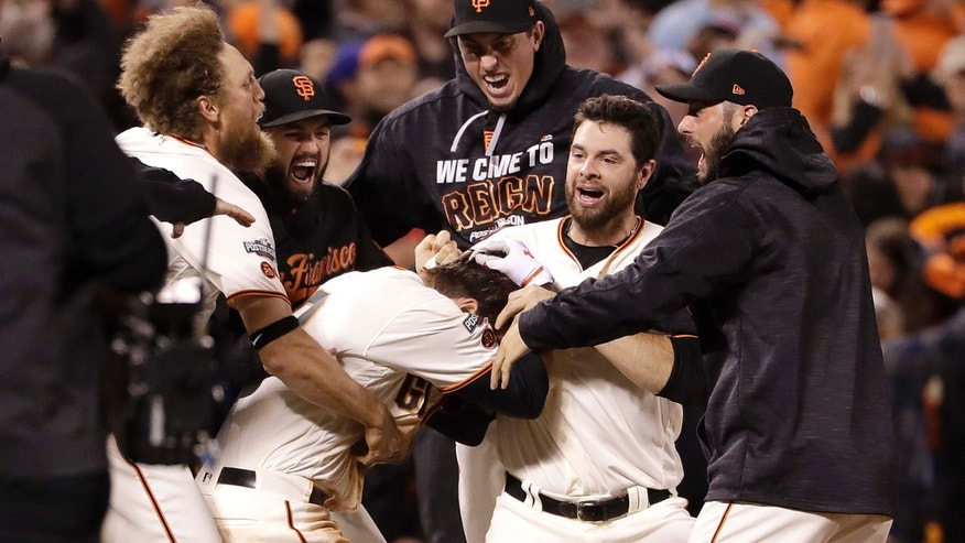 Oct. 10, 2016: San Francisco Giants' Joe Panik, center bottom, is congratulated by teammates after hitting a double to score Brandon Crawford during the thirteenth inning of Game 3 of baseball's National League Division Series against the Chicago Cubs in San Francisco.