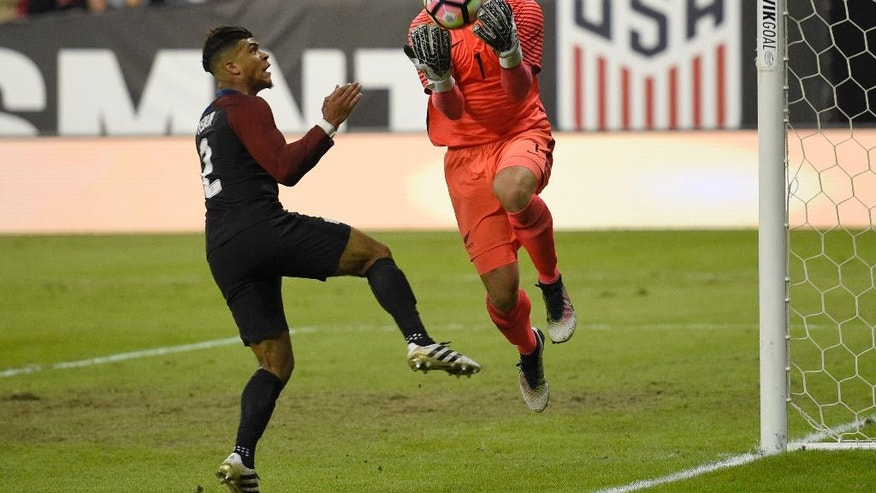 New Zealand goalkeeper Stefan Marinovic (1) catches the ball next to U.S. defender DeAndre Yedlin (2) during the first half of an international friendly soccer match Tuesday, Oct. 11, 2016, in Washington. (AP Photo/Nick Wass)