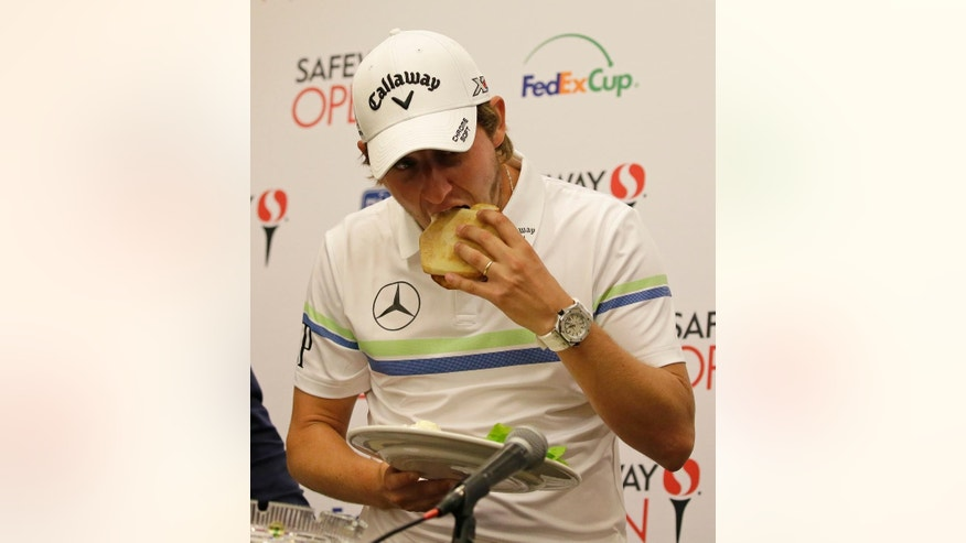 Emiliano Grillo, of Argentina, takes a bite of a special sandwich made just for him after being named the Rookie of the Year at the Silverado Resort during the Safeway Open PGA golf tournament Wednesday, Oct. 12, 2016, in Napa, Calif. Grillo is the defending champion of the tournament. (AP Photo/Eric Risberg)