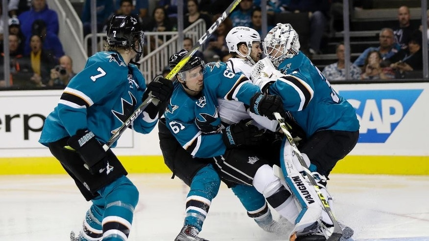 Los Angeles Kings' Kyle Clifford, center, collides with San Jose Sharks goalie Martin Jones, right, and Sharks' Justin Braun (61) during the second period of an NHL hockey game Wednesday, Oct. 12, 2016, in San Jose, Calif. (AP Photo/Marcio Jose Sanchez)