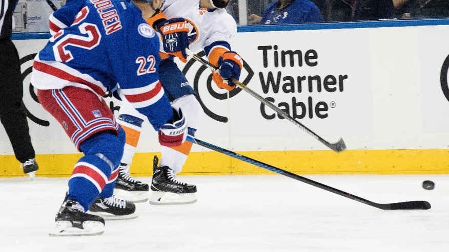 New York Islanders defenseman Nick Leddy, right, sends the puck past New York Rangers defenseman Nick Holden (22) during the first period of an NHL hockey game, Thursday, Oct. 13, 2016, at Madison Square Garden in New York. (AP Photo/Mary Altaffer)