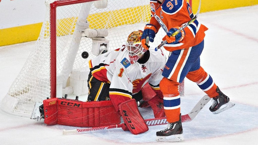Calgary Flames goalie Brian Elliott (1) is scored on by Edmonton Oilers' Connor McDavid (97) during the second period of an NHL hockey game Wednesday, Oct. 12, 2016, in Edmonton, Alberta. (Jason Franson/The Canadian Press via AP)
