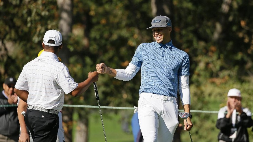 Golden State Warriors' Stephen Curry, right, greets playing partner Harold Varner III, left, on the 14th green of the Silverado Resort North Course during the pro-am event of the Safeway Open PGA golf tournament Wednesday, Oct. 12, 2016, in Napa, Calif. (AP Photo/Eric Risberg)