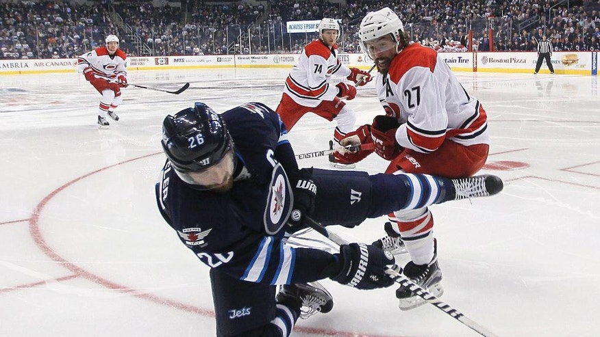 Winnipeg Jets' Blake Wheeler (26) gets dumped by Carolina Hurricanes' Justin Faulk (27) as Jaccob Slavin watches during the second period of an NHL hockey game Thursday, Oct. 13, 2016, in Winnipeg, Manitoba. (John Woods/The Canadian Press via AP)