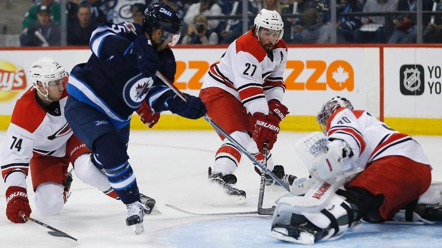 Winnipeg Jets' Mathieu Perreault (85) takes a shot on Carolina Hurricanes goaltender Cam Ward (30) as Jaccob Slavin (74) and Justin Faulk (27) defend during the second period of an NHL hockey game Thursday, Oct. 13, 2016, in Winnipeg, Manitoba. (John Woods/The Canadian Press via AP)