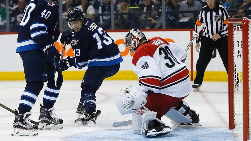 Carolina Hurricanes goaltender Cam Ward (30) saves a backhander from Winnipeg Jets' Brandon Tanev (13) as Joel Armia (40) looks for a rebound during the second period of an NHL hockey game Thursday, Oct. 13, 2016, in Winnipeg, Manitoba. (John Woods/The Canadian Press via AP)