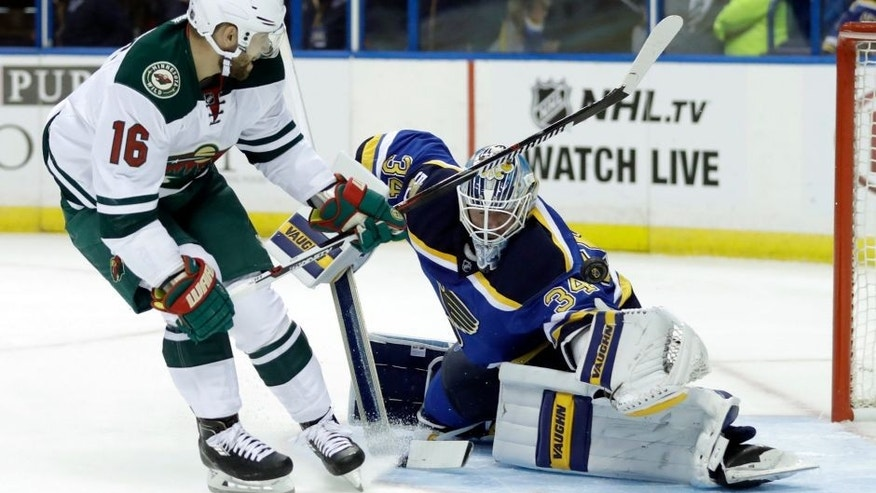 St. Louis Blues goalie Jake Allen, right, deflects a shot from Minnesota Wild's Jason Zucker during the first period of an NHL hockey game Thursday, Oct. 13, 2016, in St. Louis. (AP Photo/Jeff Roberson)