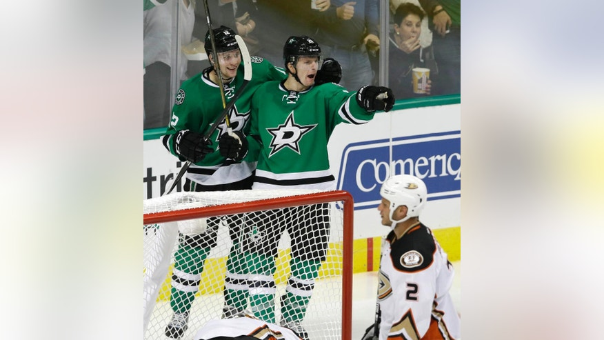 Dallas Stars left wing Antoine Roussel, right rear, celebrates his goal with teammate Radek Faksa (12) as Anaheim Ducks defenseman Kevin Bieksa (2) skates by during the third period of an NHL hockey game Thursday, Oct. 13, 2016, in Dallas. The Stars won 4-2. (AP Photo/LM Otero)