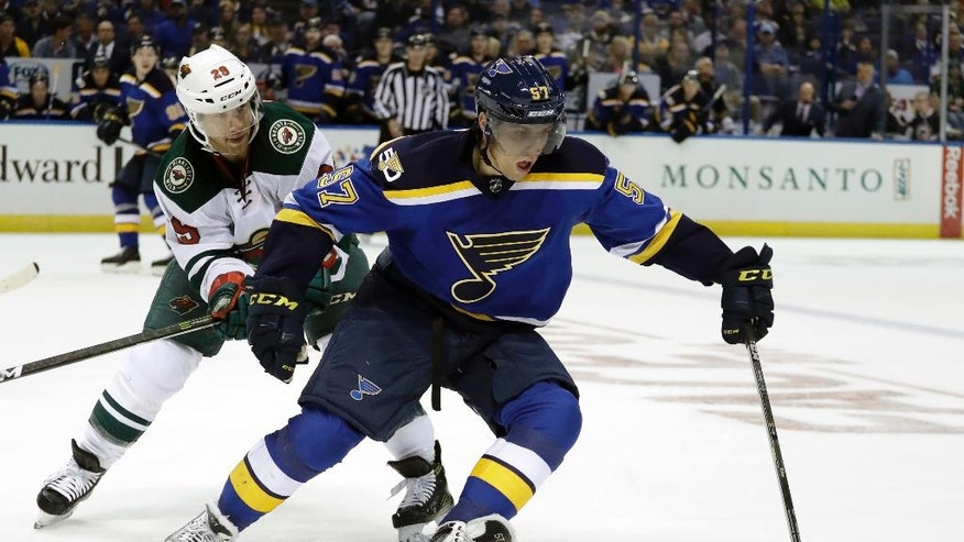 St. Louis Blues's David Perron, right, controls the puck as Minnesota Wild's Jason Pominville defends during the second period of an NHL hockey game Thursday, Oct. 13, 2016, in St. Louis. (AP Photo/Jeff Roberson)