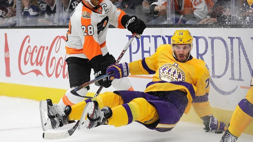 Los Angeles Kings left wing Dwight King, right, takes a tumble in front of Philadelphia Flyers center Claude Giroux during the second period of an NHL hockey game Friday, Oct. 14, 2016, in Los Angeles. (AP Photo/Jae C. Hong)