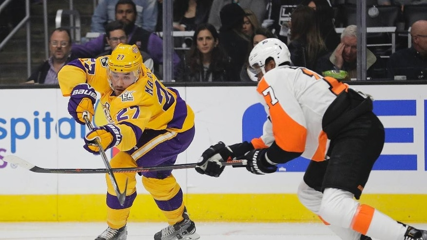 Los Angeles Kings' Alec Martinez, left, moves the puck under pressure by Philadelphia Flyers' Wayne Simmonds during the first period of an NHL hockey game Friday, Oct. 14, 2016, in Los Angeles. (AP Photo/Jae C. Hong)