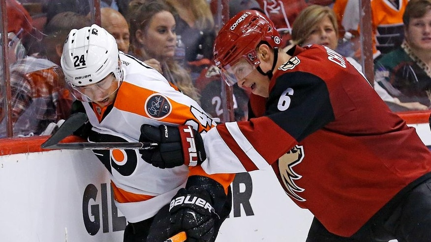 Arizona Coyotes' Jakob Chychrun (6) checks Philadelphia Flyers' Matt Read (24) into the boards during the second period of an NHL hockey game, Saturday, Oct. 15, 2016, in Glendale, Ariz. (AP Photo/Ross D. Franklin)