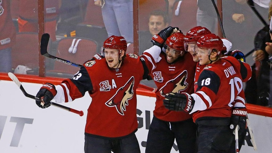 Arizona Coyotes' Oliver Ekman-Larsson (23), Christian Dvorak (18) and Anthony Duclair (10) celebrate a goal by Shane Doan, second from right, against the Philadelphia Flyers during the first period of an NHL hockey game, Saturday, Oct. 15, 2016, in Glendale, Ariz. (AP Photo/Ross D. Franklin)
