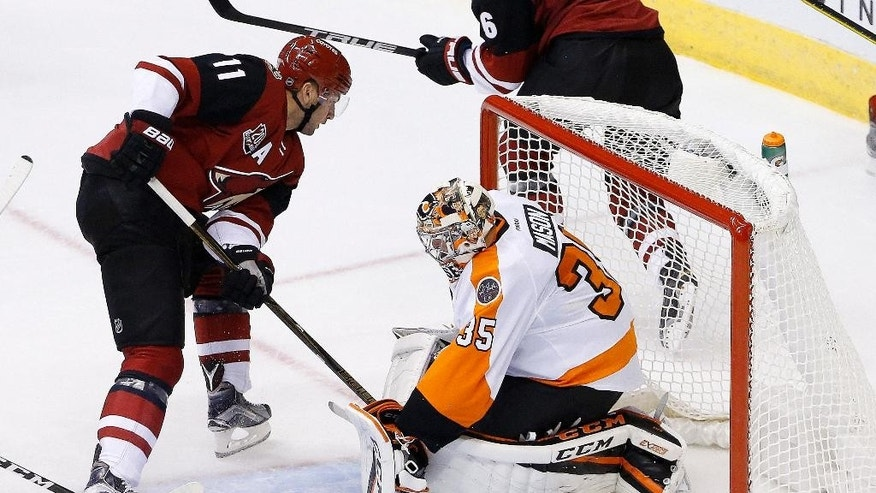 Arizona Coyotes' Martin Hanzal (11) scores a goal against Philadelphia Flyers' Steve Mason (35) during the first period of an NHL hockey game Saturday, Oct. 15, 2016, in Glendale, Ariz. (AP Photo/Ross D. Franklin)