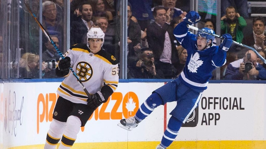 Boston Bruins' Noel Acciari, left, skates on as Toronto Maple Leafs' Mitch Marner celebrates after scoring during the first period of an NHL hockey game, in Toronto, Saturday, Oct. 15, 2016. (Chris Young/The Canadian Press via AP)