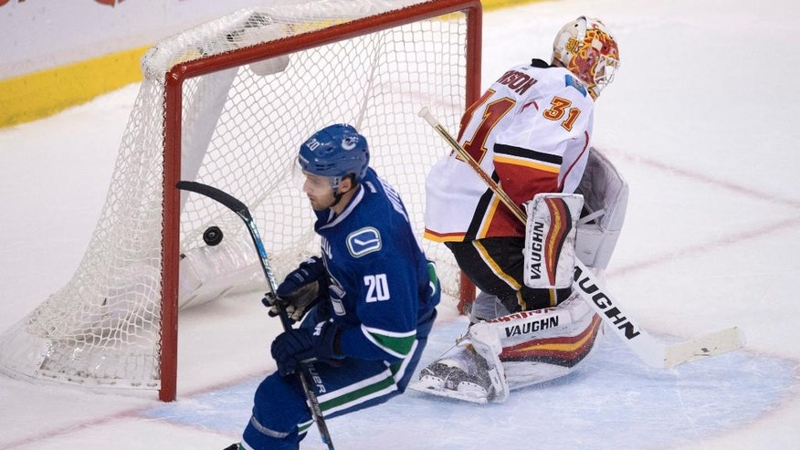 Vancouver Canucks center Brandon Sutter (20) puts his game winning shot past Calgary Flames goalie Chad Johnson (31) following the shootout of an NHL hockey game in Vancouver on Saturday, Oct. 15, 2016. (Jonathan Hayward/The Canadian Press via AP)
