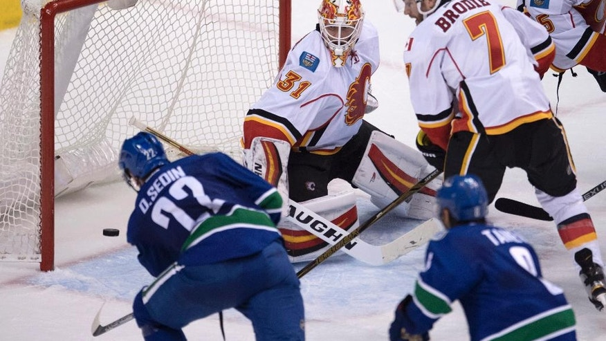 Vancouver Canucks left wing Daniel Sedin (22) puts a shot past Calgary Flames goalie Chad Johnson (31) as Calgary Flames defenseman TJ Brodie (7) looks on during the third period of an NHL hockey game in Vancouver on Saturday, Oct. 15, 2016. (Jonathan Hayward/The Canadian Press via AP)
