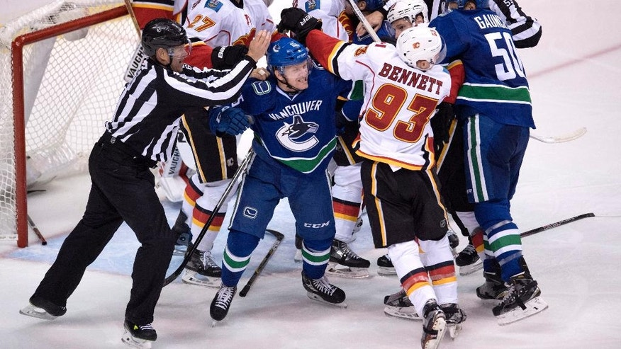 Vancouver Canucks mix it up with the Calgary Flames in front of the Calgary net during the third period of an NHL hockey game in Vancouver on Saturday, Oct. 15, 2016. (Jonathan Hayward/The Canadian Press via AP)