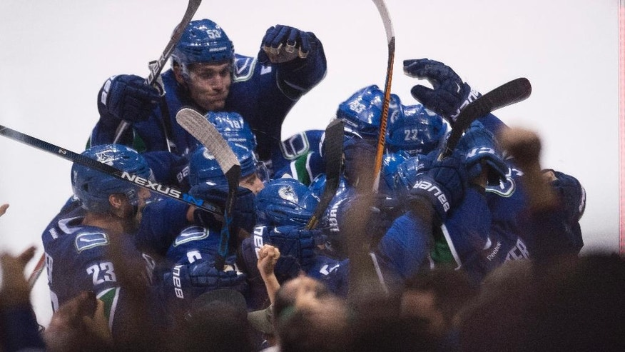 The Vancouver Canucks celebrate Brandon Sutter's game winning goal against the Carolina Hurricanes following overtime during NHL hockey action in Vancouver, British Columbia, Sunday, Oct. 16, 2016. (Jonathan Hayward/The Canadian Press via AP)